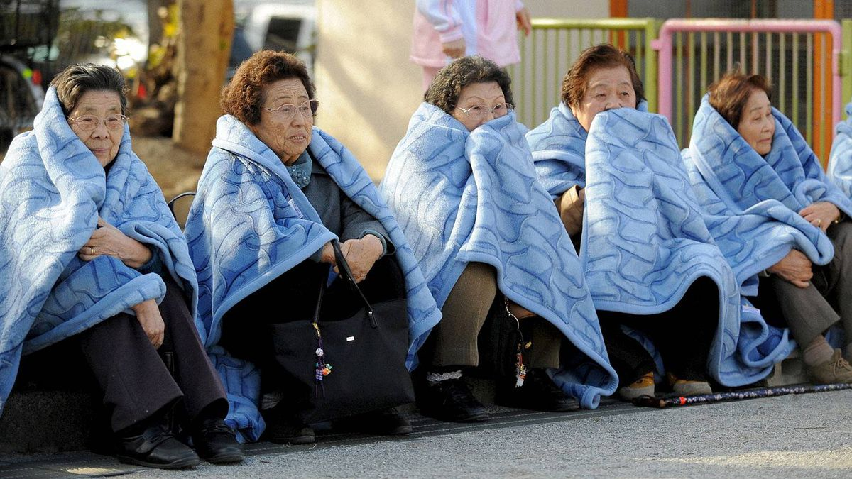 Women wait on the street after evacuating a building following an earthquake in Tokyo