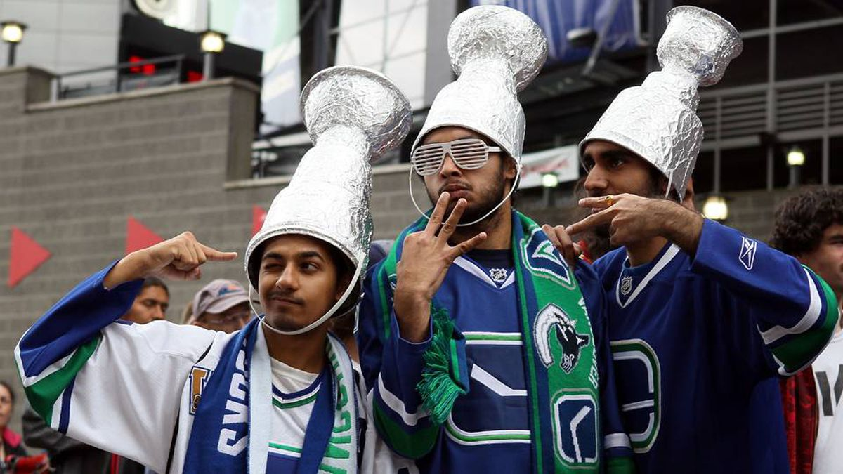 Vancouver Canucks fans Kevin Rasanti, Sarb Bolina and Sameer Bilkho pose outside of Rogers Arena prior to Game 5.
