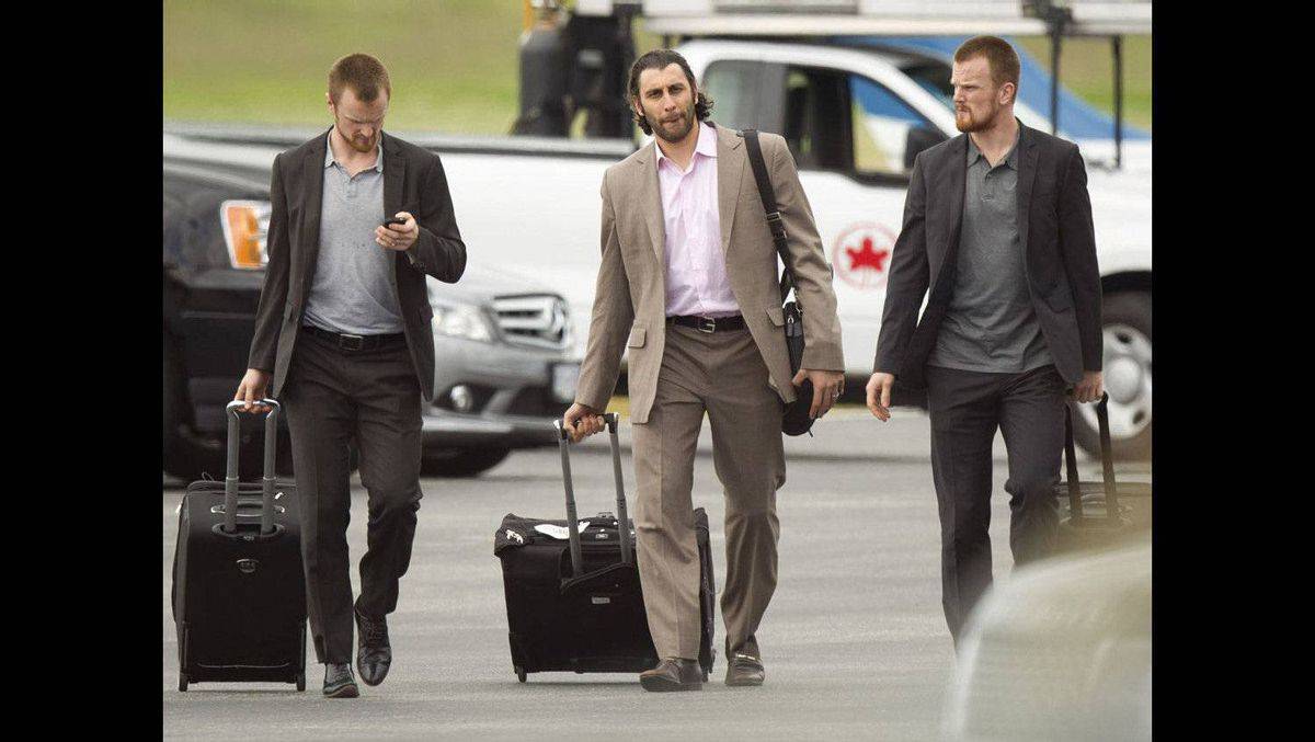Flanked buy the Sedin twins, Vancouver Canucks goalie Roberto Luongo makes his way to his car at Vancouver airport June 14, 2011 after arriving from Boston with the rest of the team.