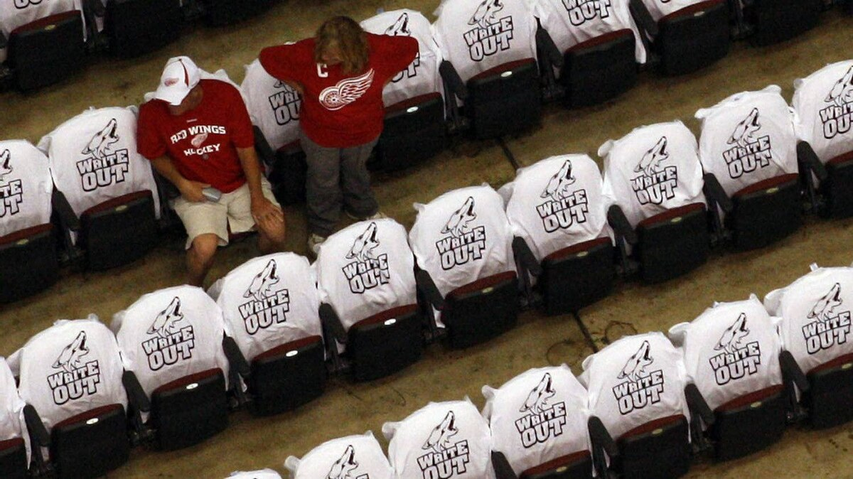 Detroit Red Wings fans take their seats surrounded by Phoenix Coyotes White Out t-shirts prior to the start of Game 3 of a first-round NHL Stanley Cup playoffs hockey series between the Red Wings and the Coyotes Monday, April 18, 2011, in Glendale, Ariz. (AP Photo/Ross D. Franklin)