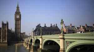 Pedestrians walk across Westminster Bridge in front of the Big Ben Clock Tower, in London March 8, 2011.