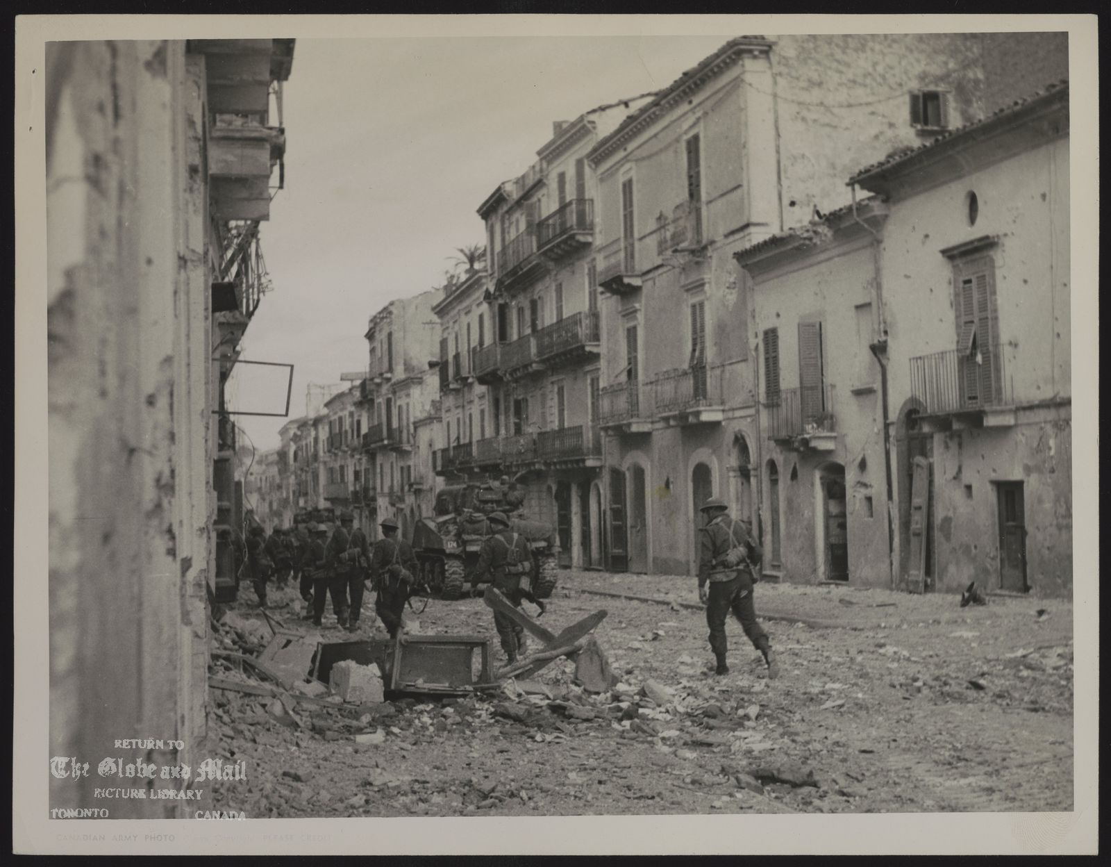 WORLD WAR II Canada Forces in Italy 27991-N-WESTERN CANADA UNIT ADVANCE IN ORTONA Victory march in Ortona. Western Canadian infantry move up rubble-piled street after driving the Germans from this bitterly defended town. (Canadian Army Overseas Photo) Item part of: Canada. Dept. of National Defence collection [Infantry of the Edmonton Regiment supported by 'Sherman' tanks of the Three Rivers Regiment, Ortona, Italy, 23 December 1943.]