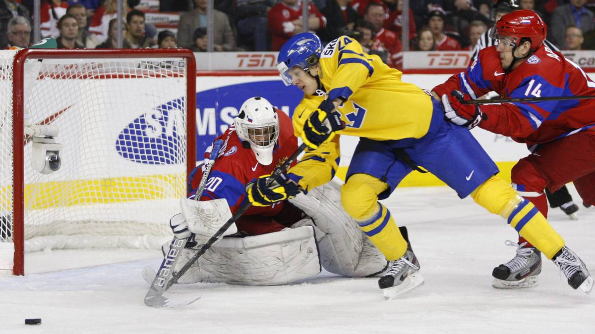Sweden's Rickard Rakell tries to get a shot past Andrei Makarov as Daniil Apalkov chases in the first period.