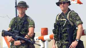 Canadian troops guard the entrance gate at Camp Mirage in the United Arab Emirates on March 19, 2003.