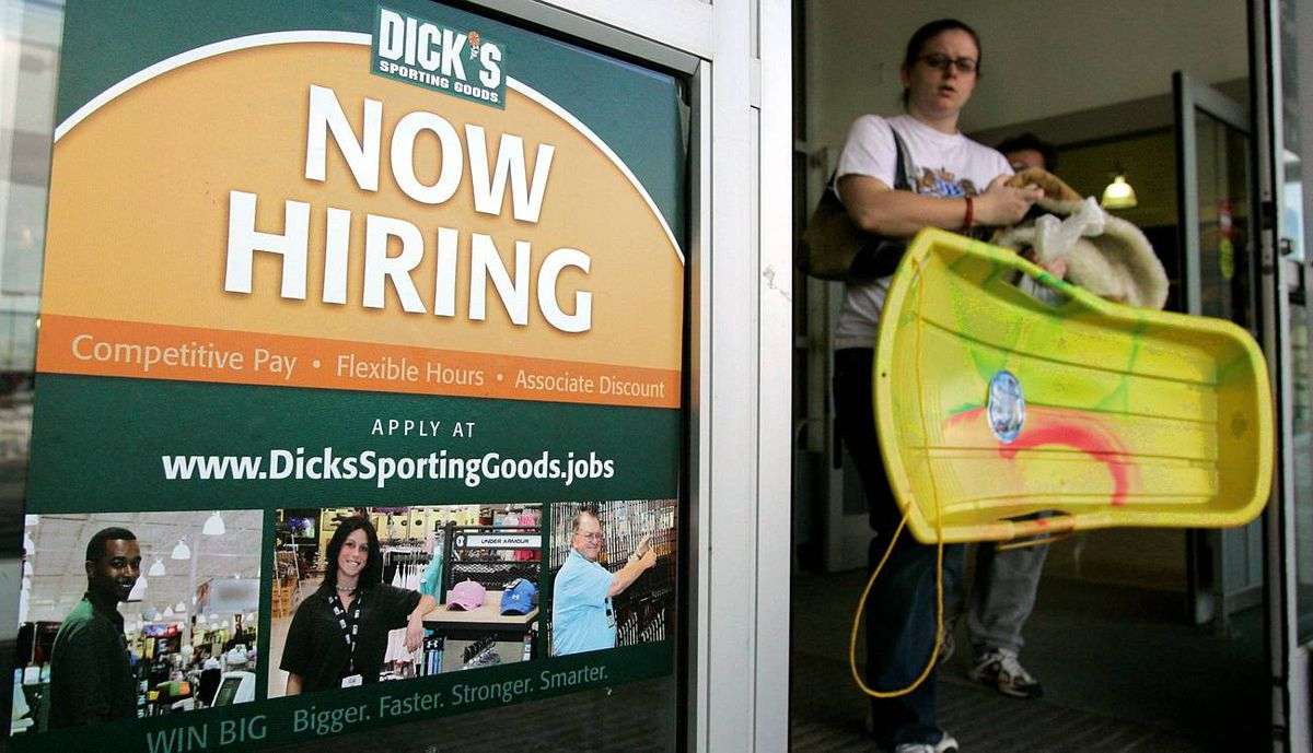 """A customer walks past a """"now hiring"""" poster on the door of a Dick's sporting goods store in in Aurora, Ohio."""