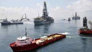 Ships and drilling rigs surround the Discoverer Enterprise as it continues to recover oil from the Deepwater Horizon drill site in the Gulf of Mexico, in this June 15, 2010 handout photo