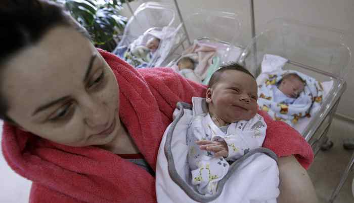 A mother holds her newborn baby at a maternity hospital in Tbilisi, October 31, 2011.