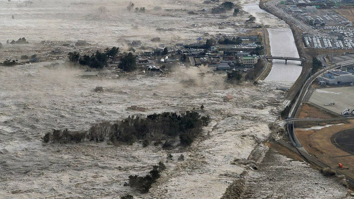 A massive tsunami hits the coastal areas of Iwanuma, Miyagi Prefecture, northeastern Japan