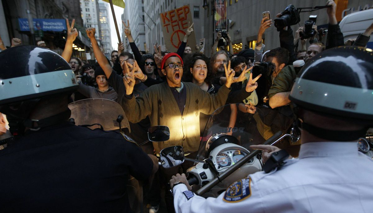 Demonstrators affiliated with the Occupy Wall Street protests confront New York City police officers as they march on the street in the Wall Street area, Friday, Oct. 14, 2011, in New York. The cleanup of a plaza in lower Manhattan where protesters have been camped out for a month was postponed early Friday, sending cheers up from a crowd that had feared the effort was merely a pretext to evict them.