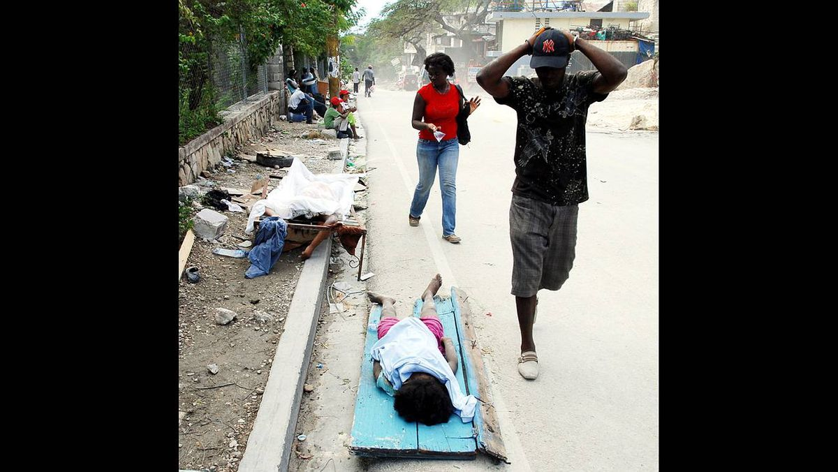 People look at bodies along the road on Jan. 13, 2010, in Port-au-Prince, Haiti.