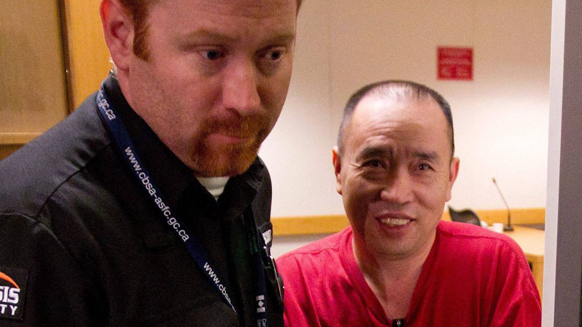 Lai Changxing, right, is shown being escorted by a security guard from an Immigration and Refugee Board detention hearing in Vancouver, B.C., on Monday July 11, 2011.