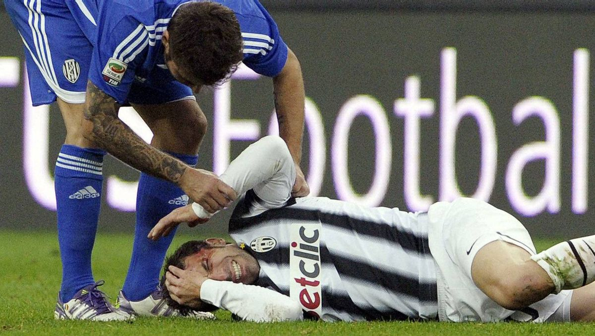 Juventus' Alessandro Del Piero lies on the field in pain as Cesena's Adrian Mutu tends to him, during a Serie A soccer match between Juventus and Cesena at the Juventus stadium in Turin, Italy, Sunday, Dec, 4 2011. Del Piero had only been on for six minutes when Cesena defender Marco Rossi appeared to land his boot near the 37-year-old forward's left temple in the 62nd minute Sunday. He was treated and released from hospital after taking eight stitches. (AP Photo/Daniele Badolato, Lapresse)