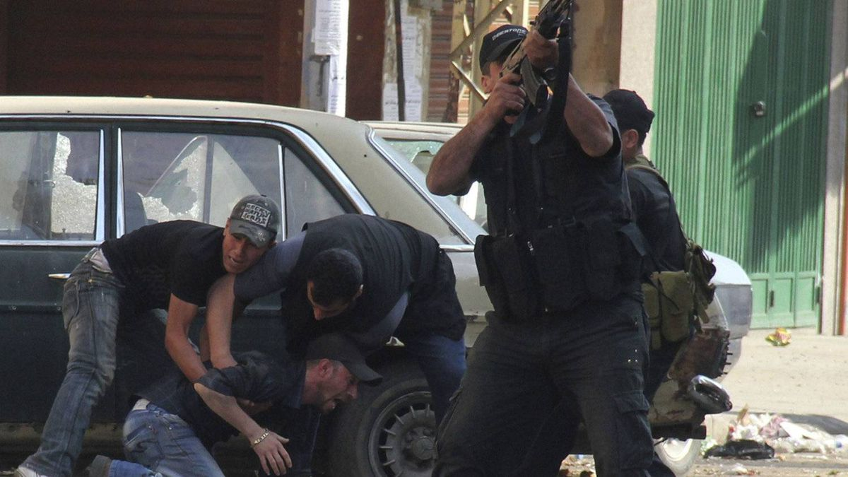 A Sunni Muslim gunman fires his rifle as others help an injured colleague during clashes at the Sunni Muslim Bab al-Tebbaneh neighbourhood in Tripoli, northern Lebanon, May 14, 2012.