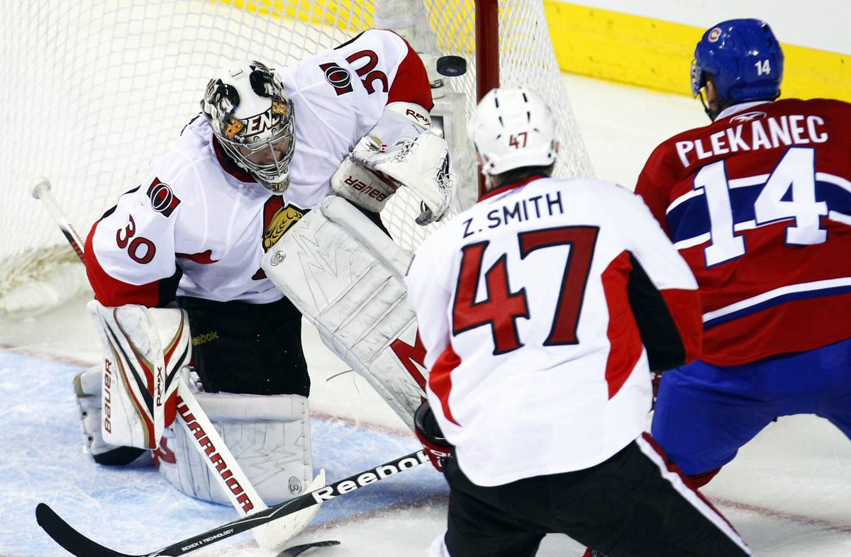 Ottawa Senators goalie Brian Elliott (L) makes a save on Montreal Canadiens' Tomas Plekanec (R) during second period of NHL hockey action in Montreal March 22, 2010.