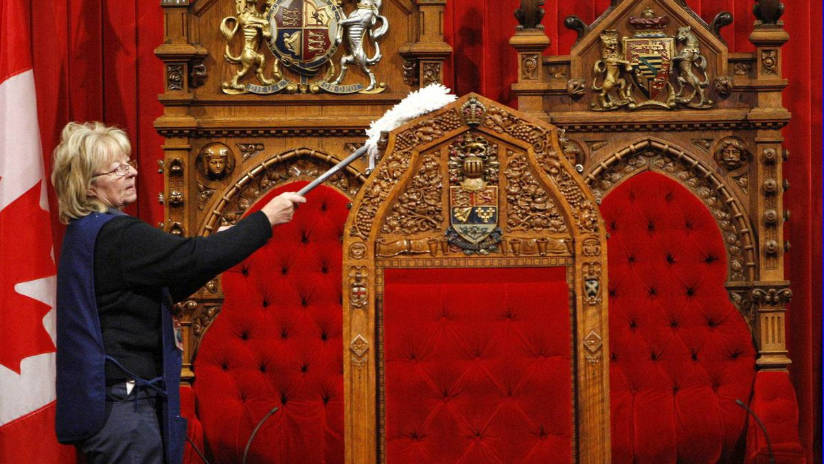 A maintenance worker cleans the Speaker's chair in the Senate chamber in preparation for the return of Parliament on Nov. 17, 2008.