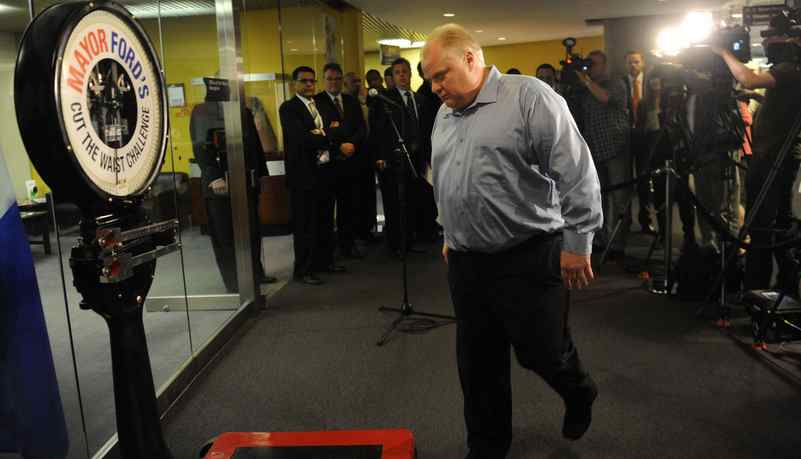 Mayor Rob Ford heads for the scale during his weekly weigh in at city hall. While weighing in, two members of PETA ( People for the Ethical Treatment of Animals) showed up offering him a vegan option to help his weight loss program.