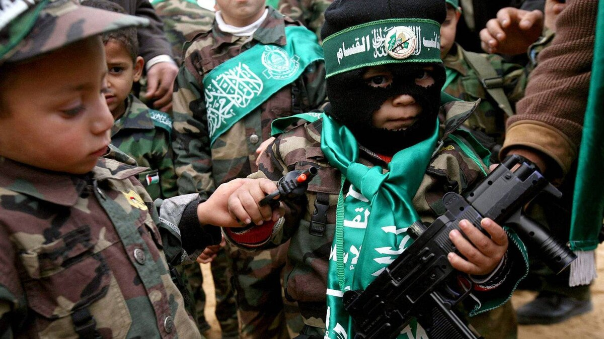 A Palestinian boy dressed as a Hamas militant holds two toy guns with other small boys wearing military uniforms bearing Hamas banners during a rally celebrating Hamas's victory in the Palestinain parliamentary elections held at the Jabalya refugee camp.