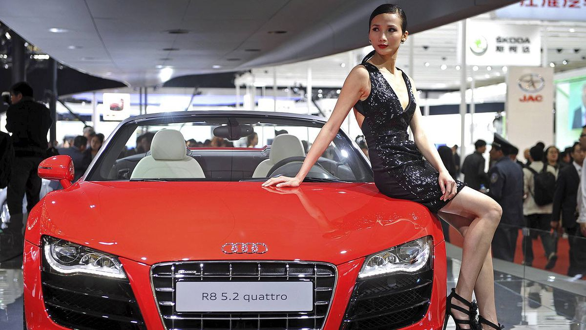 A model poses on a Audi R8 at the Shanghai Auto Show in Shanghai on April 19, 2011. About 2,000 car and parts makers from 20 countries are participating in the Shanghai auto show, showcasing 75 new car models, 19 of them making their world premieres. AFP PHOTO/Philippe Lopez (Photo credit should read PHILIPPE LOPEZ/AFP/Getty Images)