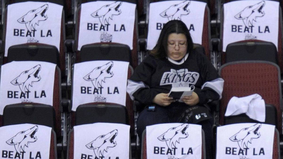 """A lone Los Angeles Kings fan sits amid a sea of """"Beat L.A."""" towels that await Phoenix Coyotes fans upon their arrival for Game 5 of the NHL Western Conference hockey finals in Glendale, Arizona, May 22, 2012. REUTERS/Todd Korol"""