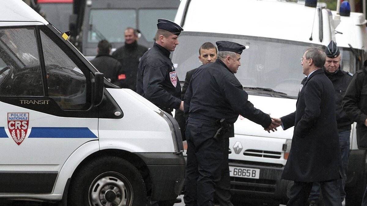 French Interior Minister Claude Gueant, right, shakes hands with a police officer as he arrives at the siege in Toulouse, on March 22, 2012.