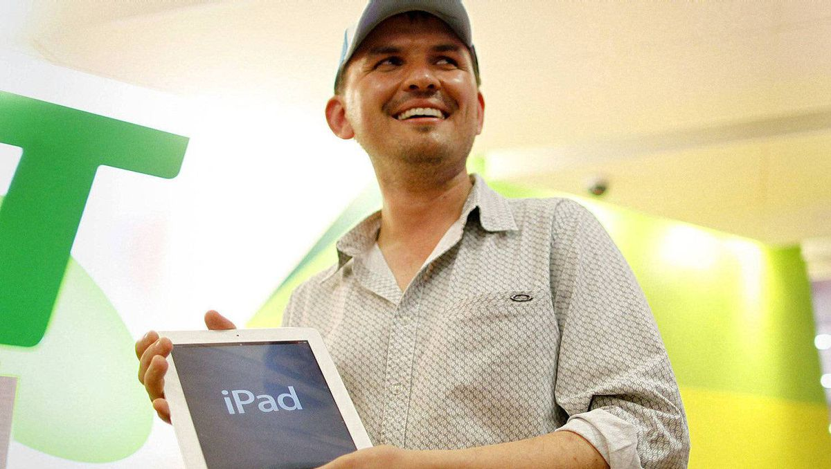 "Construction manager David Tarasenko poses with the first new iPad sold from a store in Sydney, moments after midnight, March 16, 2012. ""When Tim Cook announced it, it sounded like such a magical tool. I just got hyped into it, I guess,"" he said."