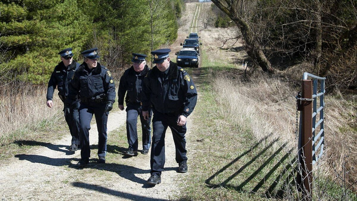 OPP officers are seen leaving the site where Tori Stafford's body was found near Mount Forest, Ont. after members of the jury in the Michael Rafferty trial were given a tour of the site, on April 2, 2012.