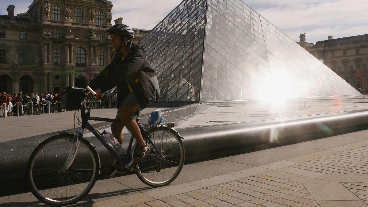 A woman rides a bicycle in front of the pyramid of the Louvre museum on August 24, 2005 in Paris.