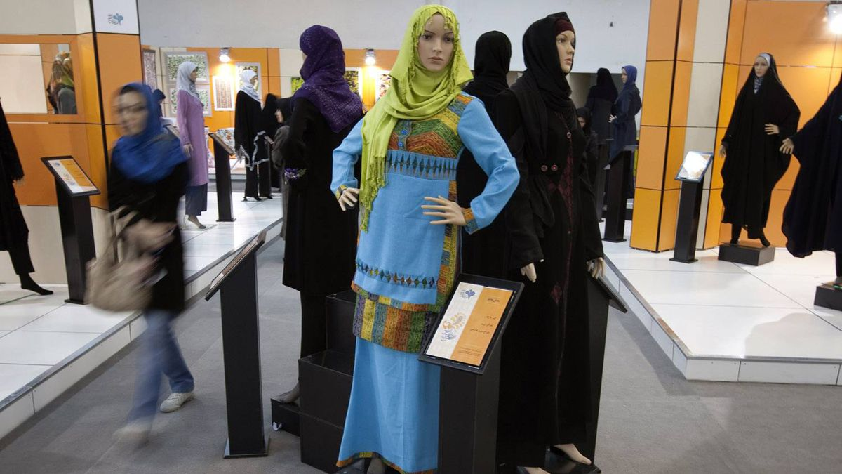 An Iranian woman walks past mannequins covered with Islamic clothing designed by Iranian designers during an Islamic fashion exhibition in central Tehran March 1, 2012.