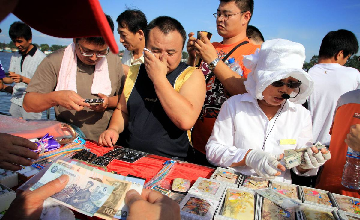 Chinese tourists buy North Korean souvenirs on a boat on the River Yalu at Dandong. China. which seperates China and North Korea.