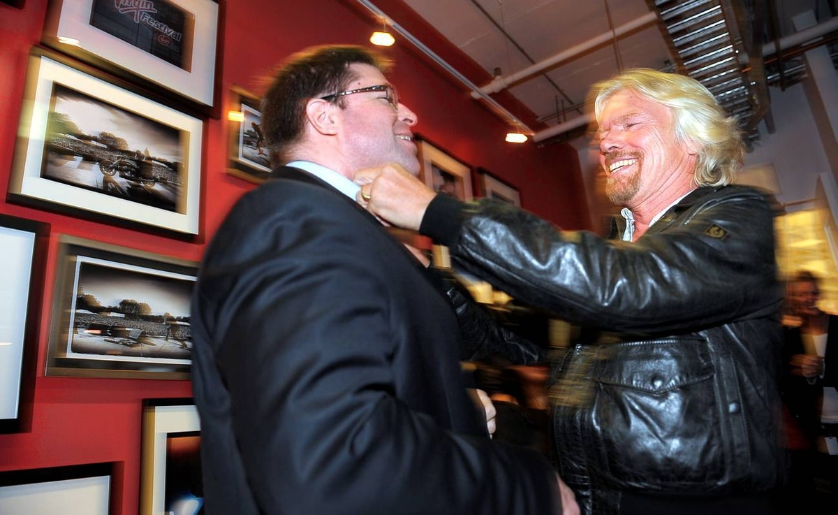 Sir Richard Branson taking part in a Virgin Mobile in-house event in downtown Toronto where awards were handed out to employees. Branson playfully loosens tie of Darren Slind, of J.D. Power and Associates.