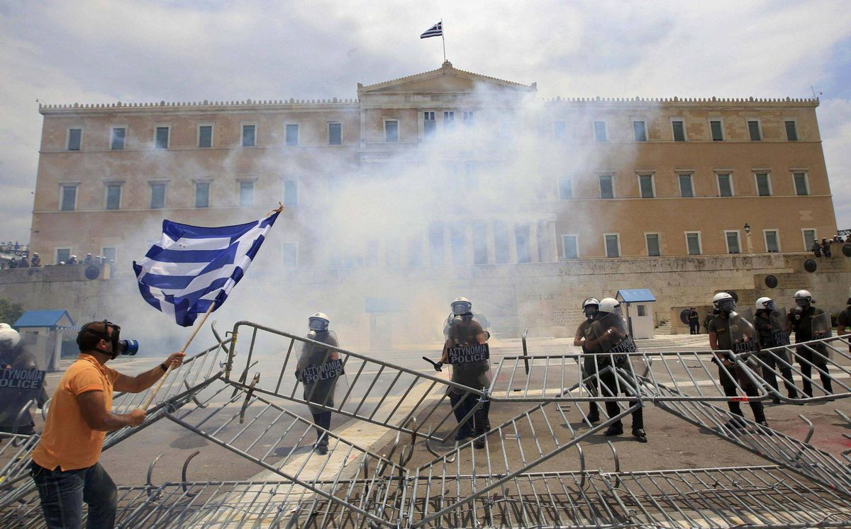 An anti-austerity protester holds a Greek flag as he confronts riot police in front of the parliament in Athens June 29, 2011. Greece's parliament looked increasingly likely to approve unpopular austerity measures on Wednesday, despite violent protests, to secure international funds to prevent the euro zone's first sovereign default. REUTERS/John Kolesidis (GREECE - Tags: CONFLICT SOCIETY POLITICS BUSINESS)
