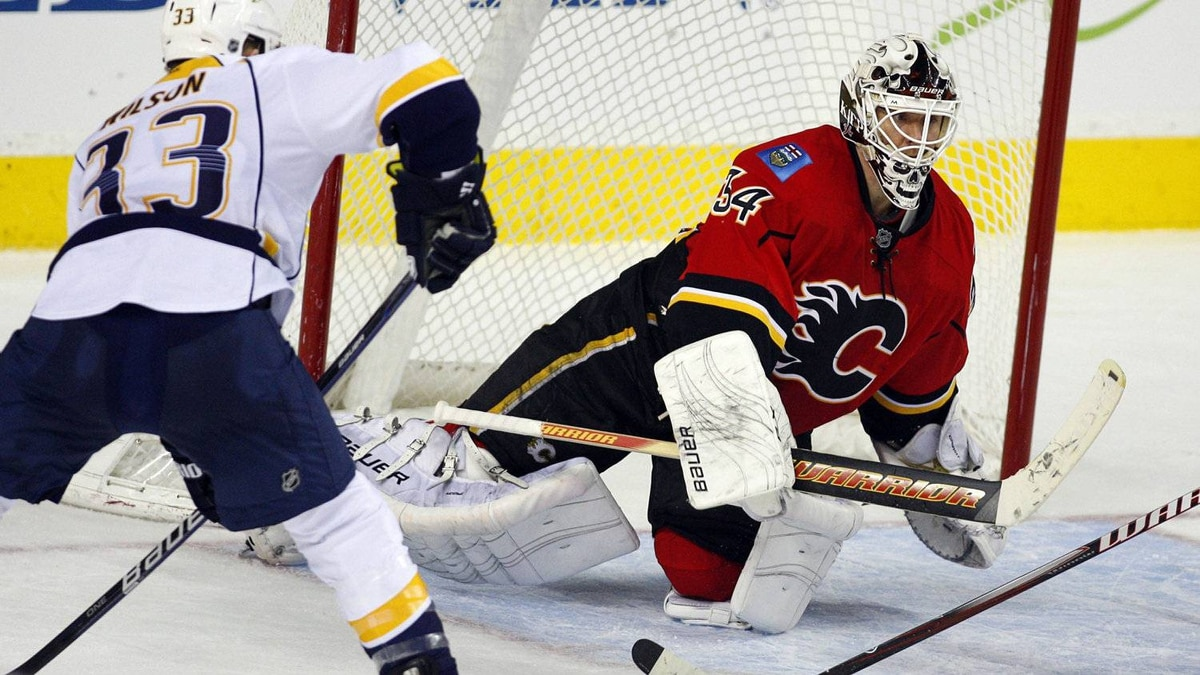 Nashville Predators' Colin Wilson, left, looks on as Calgary Flames goalie Miikka Kiprusoff, from Finland, swats away the puck during third period NHL hockey action in Calgary, Alta., Tuesday, Nov. 29, 2011. The Calgary Flames beat the Nashville Predators 1-0.THE CANADIAN PRESS/Jeff McIntosh