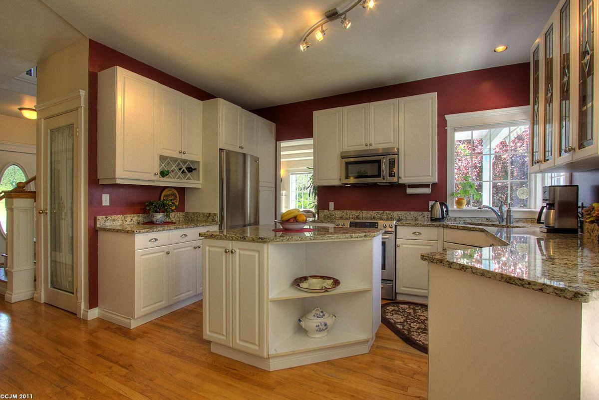 The open concept kitchen has granite counter tops and stainless steel appliances.