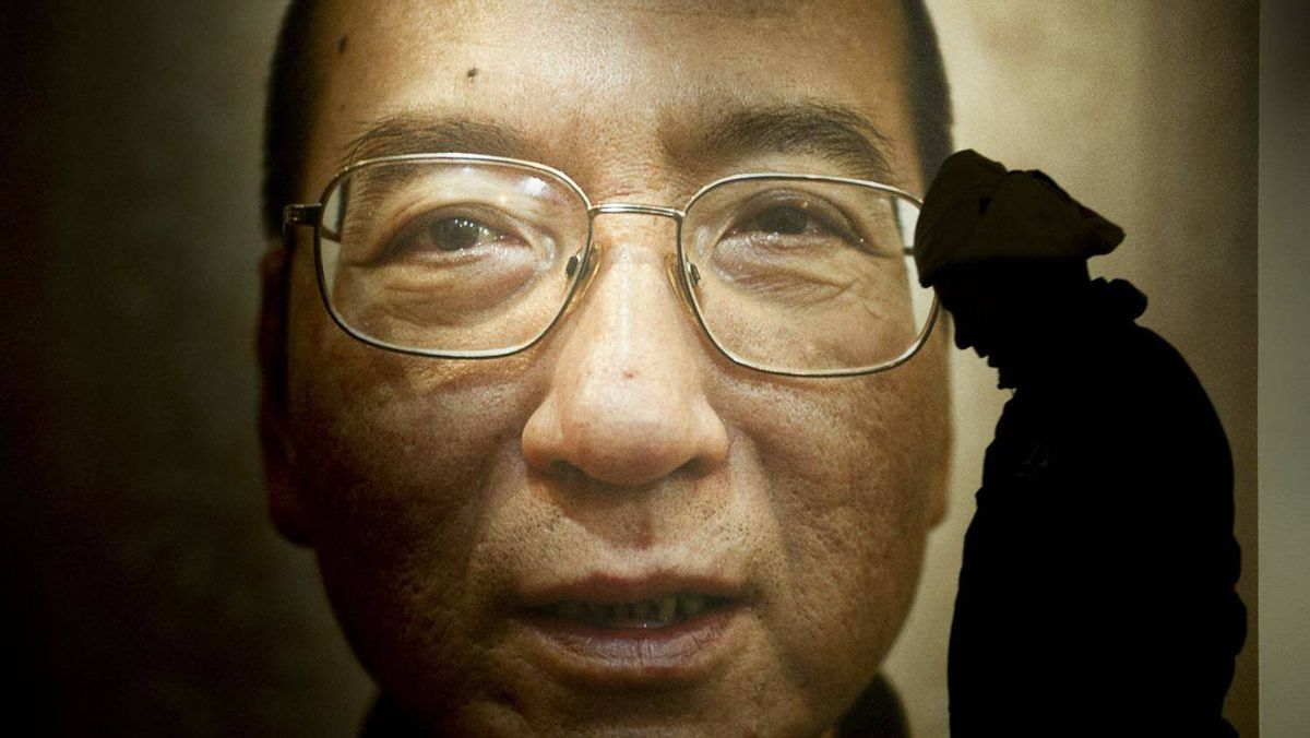 A man walks in front of a poster of Chinese dissident and peace prize laureate Liu Xiaobo at an exhibition at the Nobel Peace Center in Oslo, December 9, 2010.
