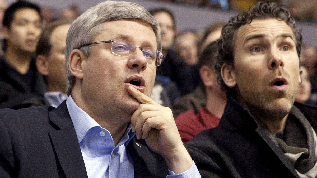 Canadian Prime Minister Stephen Harper and former Vancouver Canuck Trevor Linden react while watching the Vancouver Canucks take on the Minnesota Wild in Vancouver, British Columbia March 14, 2011. REUTERS/Ben Nelms