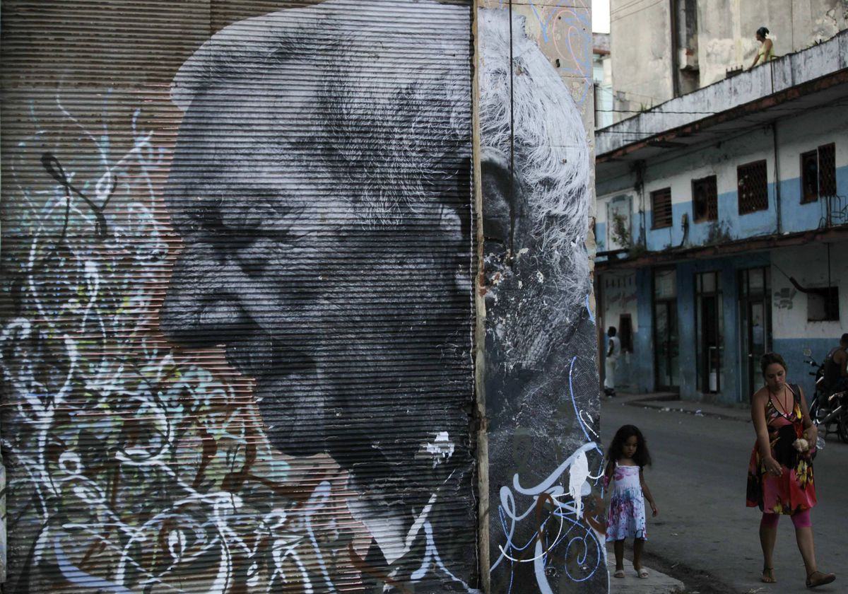 People walk beside a creation by Cuban-American artist Jose Parla and French artist J.R. on a street wall in Havana, which is part of the upcoming 11th Havana Biennial contemporary art exhibition.