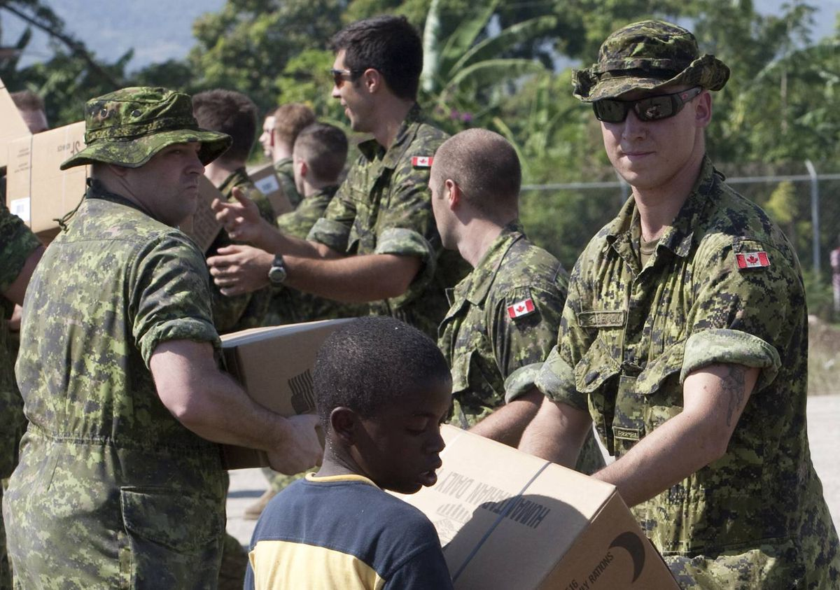 Canadian soldiers get help from local residents as they move humanitarian aid at the airport in Jacmel, Haiti, on Wednesday, January 20, 2010.