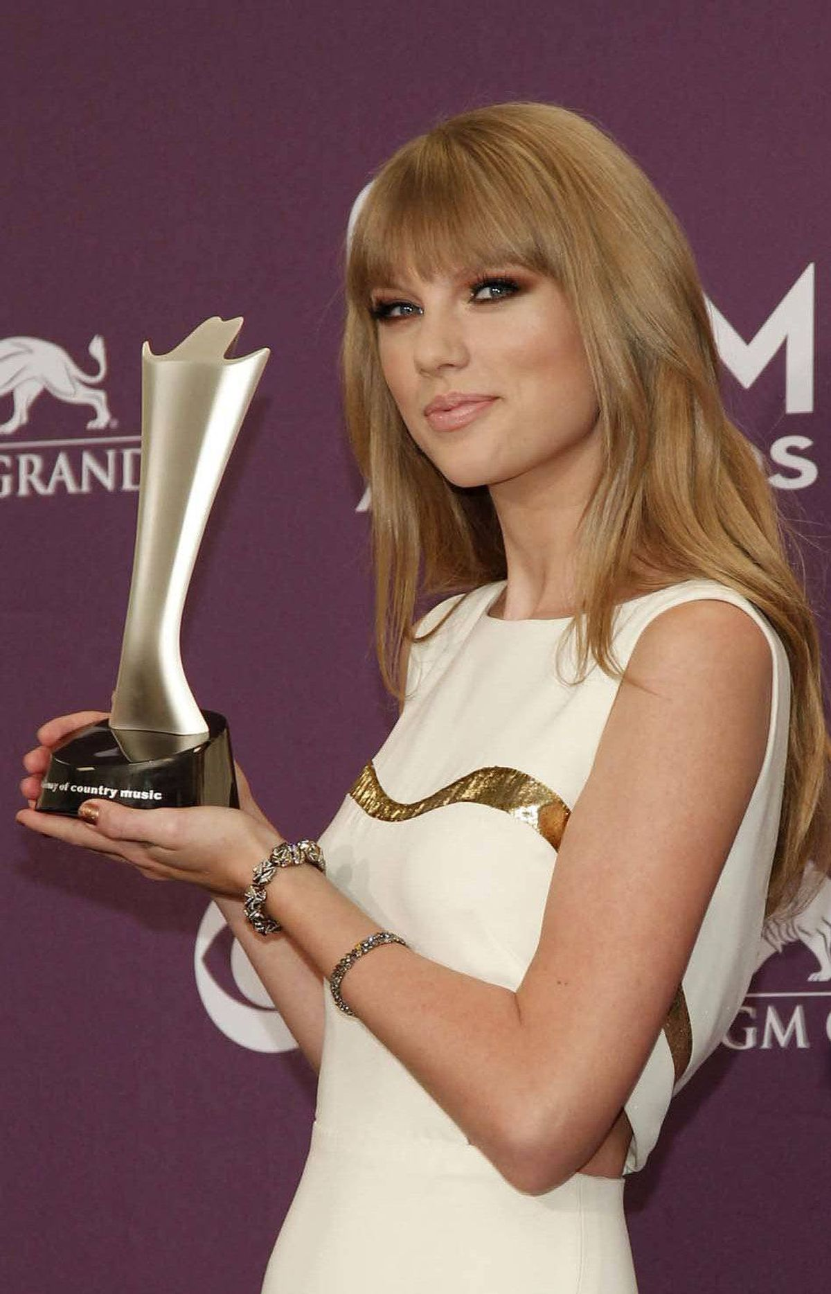 "Meanwhile, at the Academy of Country Music Awards in Las Vegas on Sunday, spokesmodel Taylor Swift poses with this year's elegant, streamlined trophy. ""It's suitable for any use and would look great in your rec room!"" Swift said."