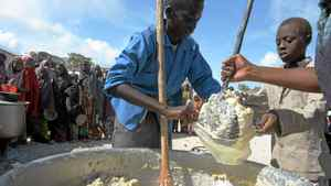 A Somali boy receives a ration of cornmeal in Mogadishu on August 15, 2011, in the courtyard of a Somali Non-governmental Organization who is partnered with the World Food Program.