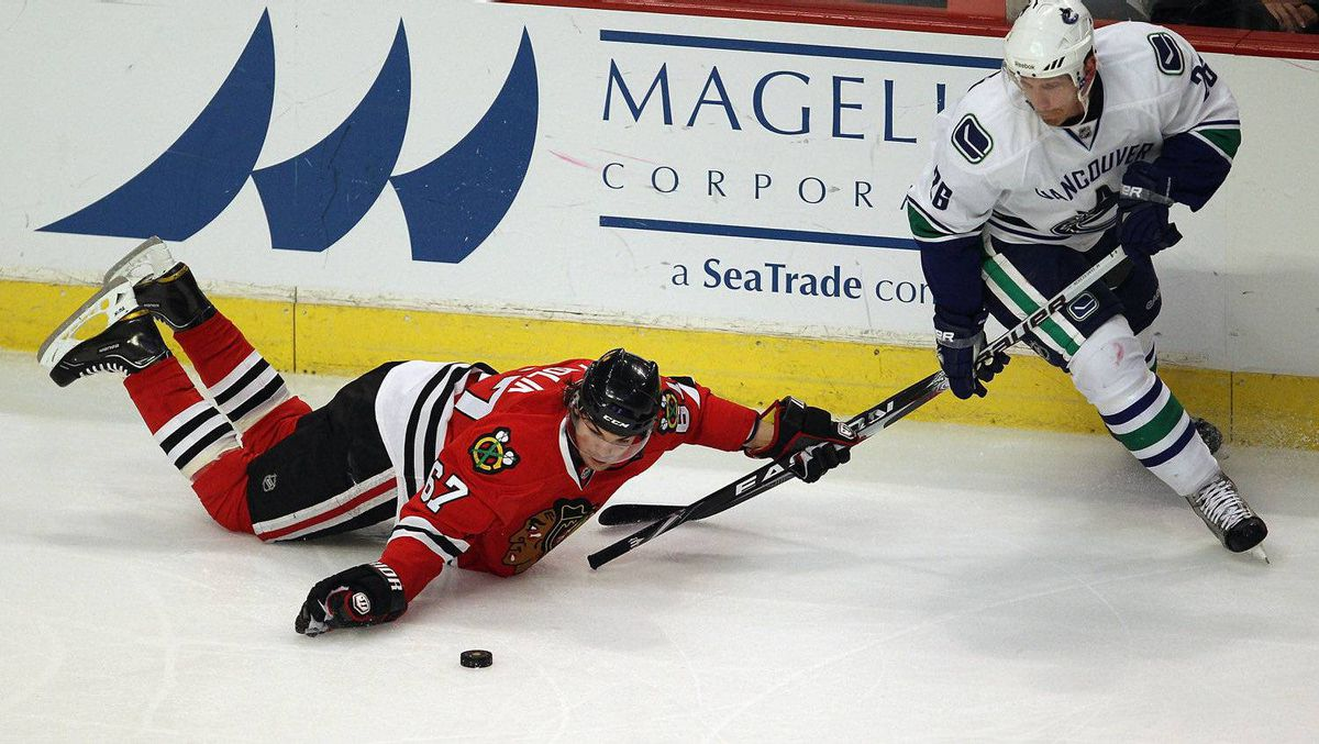 Michael Frolik #67 of the Chicago Blackhawks moves the puck forward with his hand while holding the stick of Mikael Samuelsson #26 of the Vancouver Canucks. (Photo by Jonathan Daniel/Getty Images)