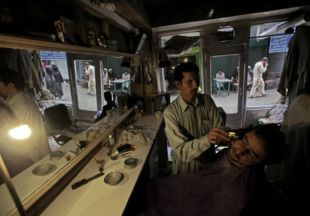 Pakistani barber Mohammed Arif, 35, lights his shop with a lamp due to a power cut, while shaving a customer, in Abbottabad, Pakistan.