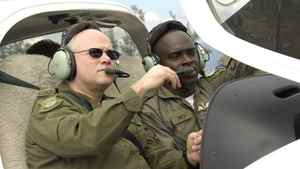 Lt.-Gen. Charles Bouchard, sits in a cockpit of a DA40 Diamond Star as he listens to Lt. Chevon Smith, in this Dec. 7, 2006 photo in Montego Bay, Jamaica.