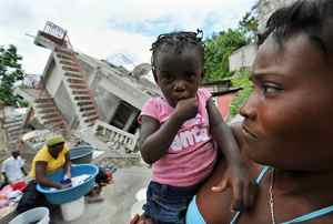 A Haitian earthquake survivor holds her child near a collapsed building in Jacmel on January 19, 2010.
