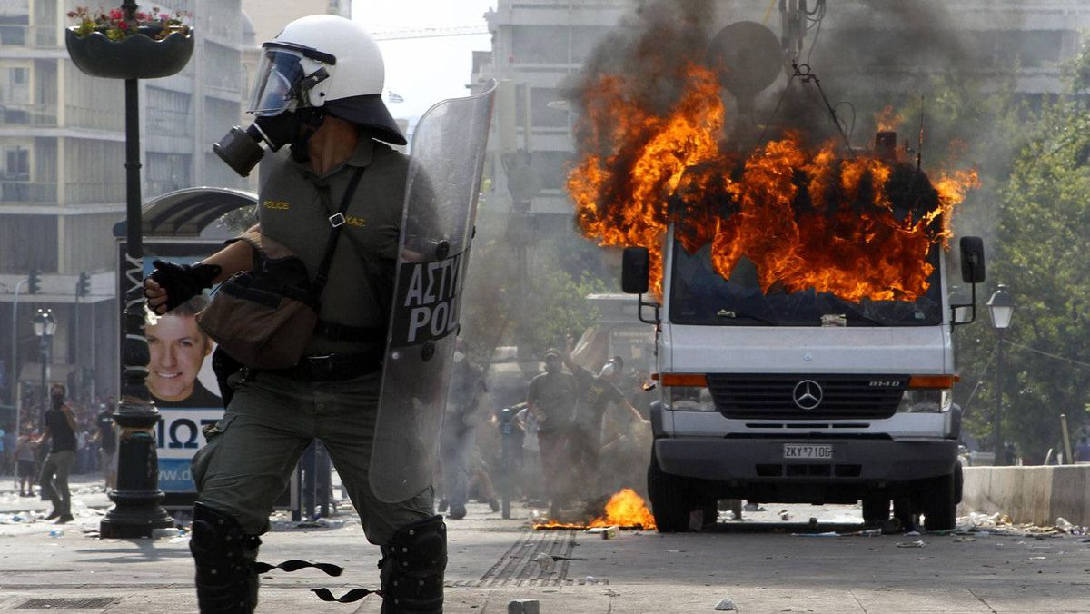 Riot policemen defend their position beside a burning van during violent protests against austerity measures in Athens' Syntagma (Constitution) square, June 28, 2011.