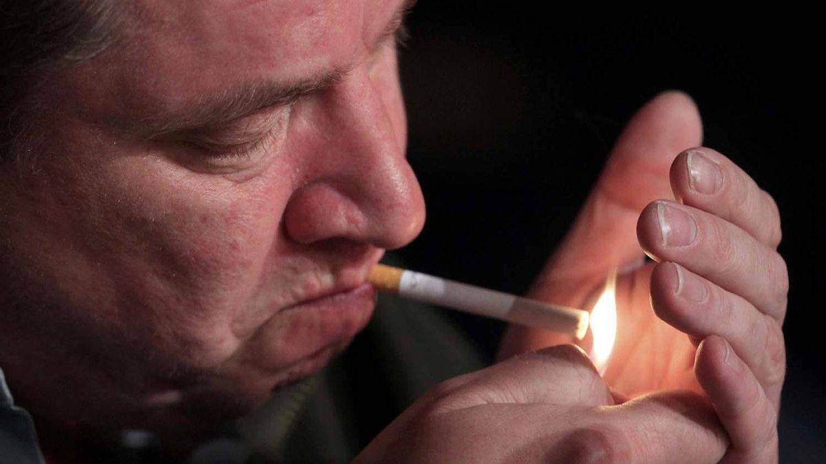 """Director Aki Kaurismaki lights a cigarette during a news conference for the film """"Le Havre"""" at the Cannes Film Festival on Tuesday."""