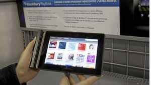 A customer looks at the BlackBerry Playbook in April, 2011. Research in Motion will report Dec. 15 on what many expect to be a grim third quarter.