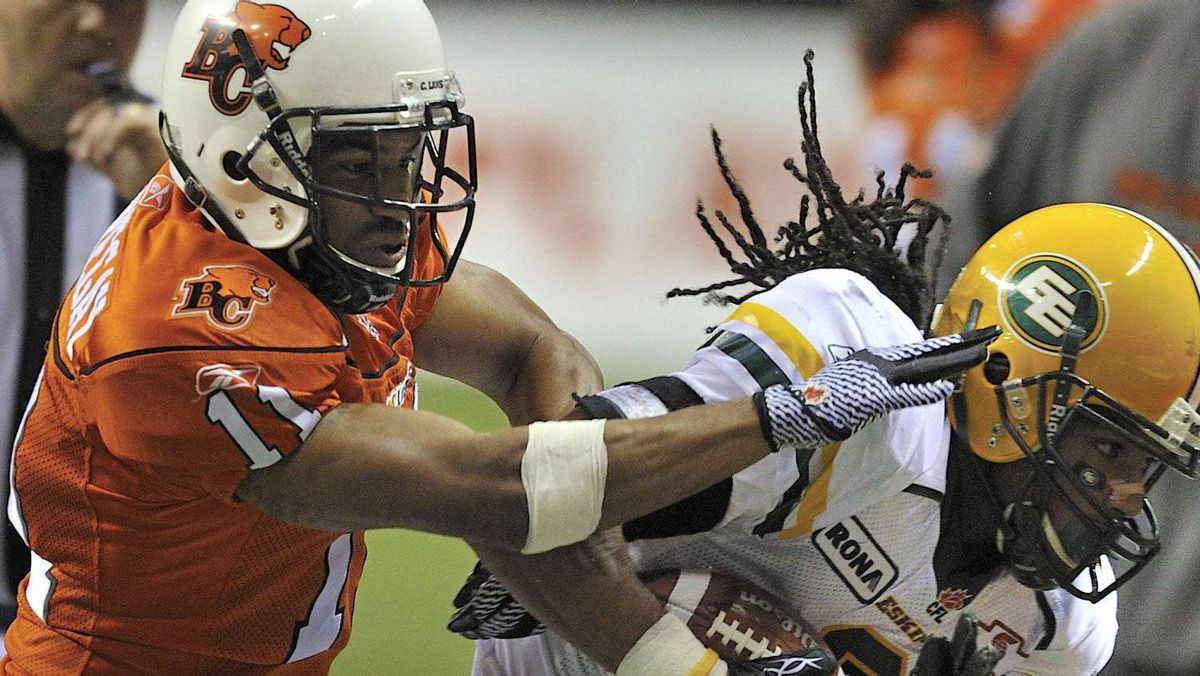 BC Lions defensive back Tad Kornegay (L) pushes Edmonton Eskimos slotback Fred Stamps (R) out of bounds during the second half of their CFL football game in Vancouver, British Columbia October 29, 2011. REUTERS/Nick Didlick