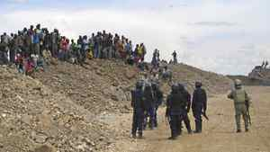 Barrick security guards (blue uniforms) and a Tanzanian police officer (green uniform) facing off against local villagers who have invaded Barrick's gold mine at North Mara, Tanzania. This confrontation, which took place last Friday, is one of the near-daily skirmishes between security forces and hundreds of villagers who are seeking waste rocks that contain small fragments of gold. Photo credit to Geoffrey York.
