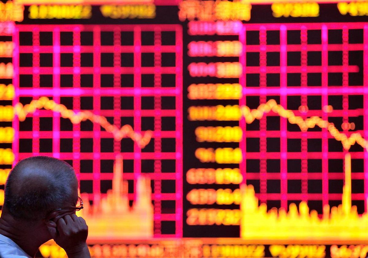 A man reads information on an electronic screen at a brokerage house in Shanghai
