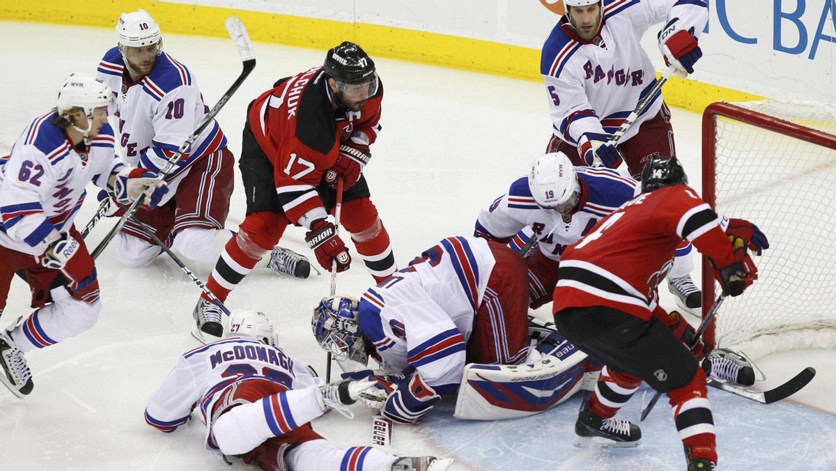 New Jersey Devils' Adam Henrique (R) scores the game winning goal on New York Rangers goalie Henrik Lundqvist in overtime in Game 6 of their NHL Eastern Conference Final hockey in Newark, New Jersey, May 25, 2012.